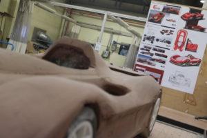 Au fond, des esquisses du prototype, avec, en gros plan, une maquette en résine.