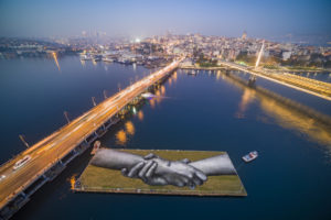 "An aerial view shows a giant landart fresco by French-Swiss artist Saype, painted for the 8th step of his worldwide ""Beyond Walls"" project on a floating barge in the Golden Horn of the Bosphorus, Istanbul, Turkey, on Friday October 23, 2020. Three frescoes were created using biodegradable pigments made out of charcoal, chalk, water and milk proteins. The ""Beyond Walls"" aims at creating the largest symbolic human chain around the world promoting values such as togetherness, kindness and openness to the world. Here in Istanbul this step links Europe to Asia : one artwork was created at Bogazici University (2500 Sq. m) on the European side of the country, a second one was created in the Beykoz district (1600 Sq. m) on the Asian side and the two of them were linked by an artwork painted on a floating barge in the Golden Horn of the Bosphorus (2200 Sq. m). (Valentin Flauraud for Saype)"