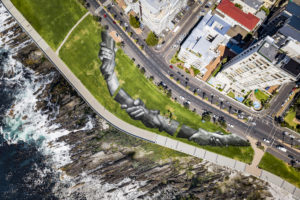 "An aerial view shows a giant landart fresco by French-Swiss artist Saype, painted for the 9th step of his worldwide ""Beyond Walls"" project in Sea Point, Cape Town, South Africa, on Monday January 18, 2021. Three frescoes were created using approximately 1000 liters of biodegradable pigments made out of charcoal, chalk, water and milk proteins. The ""Beyond Walls"" project aims at creating the largest symbolic human chain around the world, promoting values such as togetherness, kindness and openness to the world. Here in Cape Town this step was motivated by the country's persisting need for reunification. Three frescoes representing widely different populations and realities within the city were created in Sea Point (6000 Sq. m), the Philippi township (800 Sq. m) and the Langa township (800 Sq. m). (Valentin Flauraud for Saype - EDITORIAL USE ONLY)"