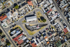 """An aerial view shows a giant landart fresco by French-Swiss artist Saype, painted for the 9th step of his worldwide """"Beyond Walls"""" project in the Langa township, Cape Town, South Africa, on Friday January 22, 2021. Three frescoes were created using approximately 1000 liters of biodegradable pigments made out of charcoal, chalk, water and milk proteins. The """"Beyond Walls"""" project aims at creating the largest symbolic human chain around the world, promoting values such as togetherness, kindness and openness to the world. Here in Cape Town this step was motivated by the country's persisting need for reunification. Three frescoes representing widely different populations and realities within the city were created in Sea Point (6000 Sq. m), the Philippi township (800 Sq. m) and the Langa township (800 Sq. m). (Valentin Flauraud for Saype - EDITORIAL USE ONLY)"""