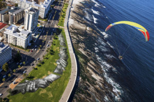 "French-Swiss artist Saype paraglides in a tandem flight above his giant landart fresco painted for the 9th step of his worldwide ""Beyond Walls"" project in Sea Point, Cape Town, South Africa, on Wednesday January 20, 2021. Three frescoes were created using approximately 1000 liters of biodegradable pigments made out of charcoal, chalk, water and milk proteins. The ""Beyond Walls"" project aims at creating the largest symbolic human chain around the world, promoting values such as togetherness, kindness and openness to the world. Here in Cape Town this step was motivated by the country's persisting need for reunification. Three frescoes representing widely different populations and realities within the city were created in Sea Point (6000 Sq. m), the Philippi township (800 Sq. m) and the Langa township (800 Sq. m). (Valentin Flauraud for Saype - EDITORIAL USE ONLY)"