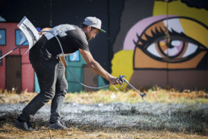 "French-Swiss artist Saype works on one of his giant landart fresco painted for the 9th step of his worldwide ""Beyond Walls"" project in the Philippi township, Cape Town, South Africa, on Wednesday January 20, 2021. Three frescoes were created using approximately 1000 liters of biodegradable pigments made out of charcoal, chalk, water and milk proteins. The ""Beyond Walls"" project aims at creating the largest symbolic human chain around the world, promoting values such as togetherness, kindness and openness to the world. Here in Cape Town this step was motivated by the country's persisting need for reunification. Three frescoes representing widely different populations and realities within the city were created in Sea Point (6000 Sq. m), the Philippi township (800 Sq. m) and the Langa township (800 Sq. m). (Valentin Flauraud for Saype - EDITORIAL USE ONLY)"